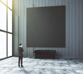 Businessman looks at blank black picturein modern room with leat