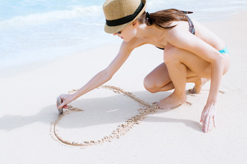 Girl drawing heart in the sand.