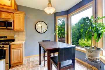 Dining breakfast table near the kitchen with blue walls.