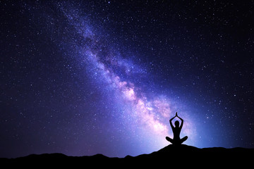 Milky Way and silhouette of a woman practicing yoga