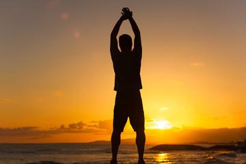 Man stretching at sunset.