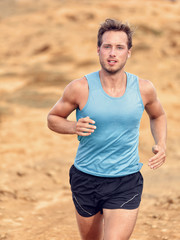Trail runner training cardio running on rocky mountains yellow sand path in nature. Caucasian male athlete waist up portrait jogging living an active healthy lifestyle exercising outdoors.