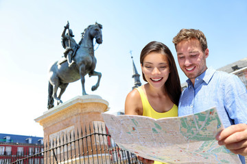 Wall Mural - Europe travel couple looking at map in Madrid. Two happy beautiful young adults looking for directions during european summer vacations in Plaza Mayor, Madrid, Spain.