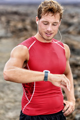 Runner looking at his heart rate monitor, activity tracker smartwatch. Active athlete looking at his smart watch using app after cardio workout for pace and distance information.