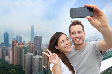 Aufkleber - Multiethnic Chinese Caucasian couple in Hong Kong. Young people taking a smartphone selfie picture at viewpoint of famous attraction Victoria Peak, HK, China. Young multiracial group of people.