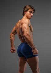Shirtless muscular man in a blue shorts.