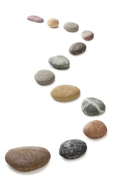A curving row of pebbles representing stepping stones, isolated on white with clipping path around pebbles.