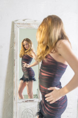 Beautiful blonde girl in a short dress looks in the mirror