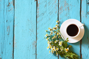 top view image of daisy flowers next to cup of coffee on blue wooden table. vintage filtered