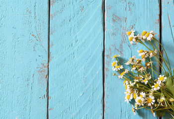 top view image of daisy flowers on blue wooden table. vintage filtered