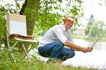 Zufriedener Maler sitzt mit Bild in der Natur