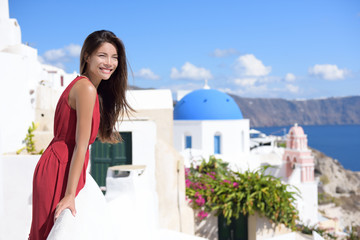 Fototapete - Santorini Thira Greece island tourism - Asian woman wearing red dress on summer travel looking at view with the famous attraction three domes chapel church in the background. Luxury destination.
