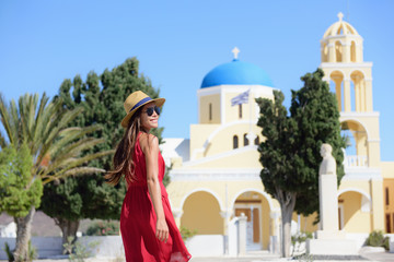 Fototapete - Santorini island Greece travel. Happy tourist woman walking in Oia village visiting blue dome church during summer vacation holidays. Beautiful young adult in fashion sun hat and red dress.