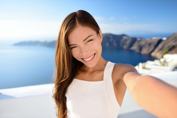 Asian beauty selfie woman on Santorini summer travel. Beautiful young adult mixed race Chinese Caucasian female model taking picture with smartphone smiling at camera. Skincare makeup concept.
