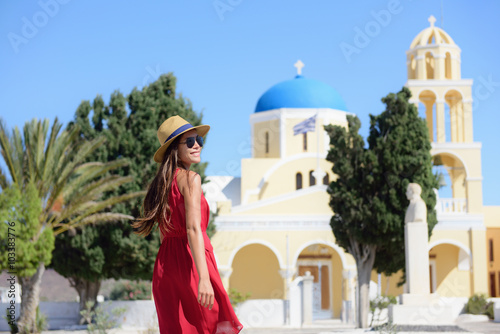 Wall mural Santorini island Greece travel. Happy tourist woman walking in Oia village visiting blue dome church during summer vacation holidays. Beautiful young adult in fashion sun hat and red dress.