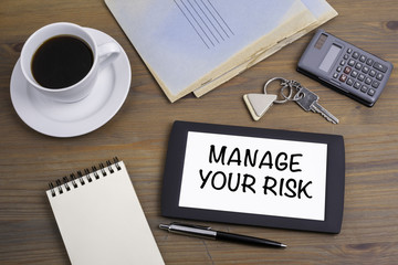Manage Your Risk. Text on tablet device on a wooden table