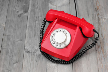 Red retro rotary phone on a wooden platform.