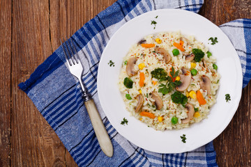 Classic Risotto with mushrooms and vegetables served on a white