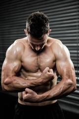 Shirtless man flexing arms