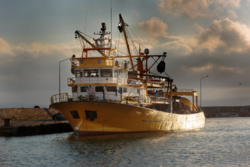 Yellow fishing boat moored to dock