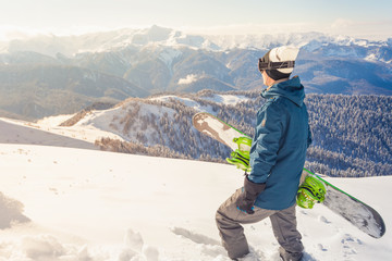 Adventure to winter sport. Snowboarder man hiking at mountain