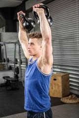 Muscular man lifting heavy kettlebells