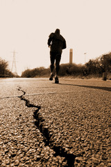 Man running on the road with cracked asphalt