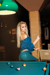 Vertical portrait of young fashionable girl posing on pool table