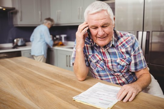 Senior man talking on phone and woman working in kitchen