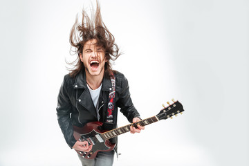 Excited young man with electric guitar shouting and shaking head