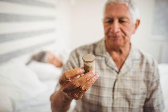 Senior man looking at a pill bottle