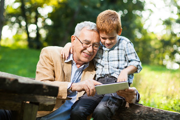 Grandfather and grandson are using digital tablet in park