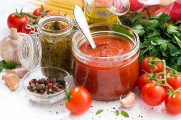 tomato sauce, pesto and ingredients for pasta on a white table