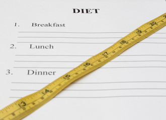 paper with day diet plan, pen and measure tape