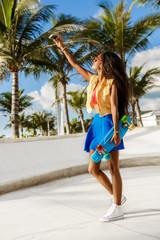 Beautiful teenage black girl in blue skirt take selfie with her