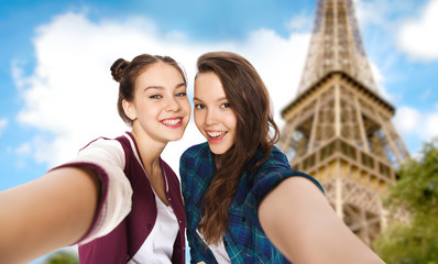 teenage girls taking selfie over eiffel tower