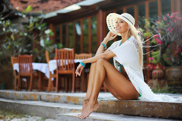 Outdoor portrait of pretty tanned young blonde woman in white dr