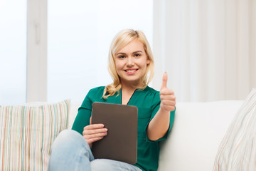 smiling woman with tablet pc at home