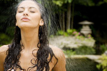 Beauty portrait of a woman in a tropical shower setting.