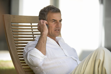 A man sitting on a sun lounger using a mobile phone