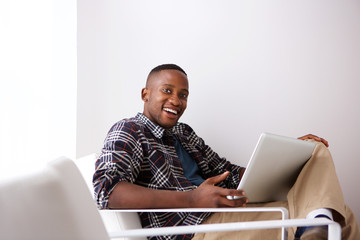 Happy young african man on arm chair with a laptop