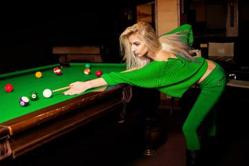 Stylish young beautiful blonde plays pool billiard