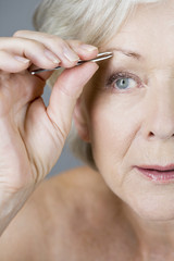 A senior woman plucking her eyebrows with tweezers