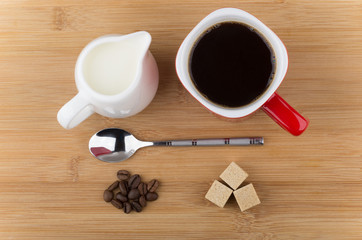 Red mug with espresso, spoon, coffee beans and milk jug