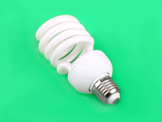 Energy saving fluorescent light bulb on green background