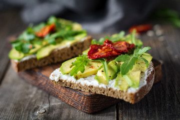 Healthy toast with goats cheese, avocado, arugula and sun dried tomatoes on rustic wooden table. Selective focus