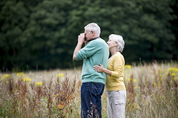 A senior couple taking photographs in a field