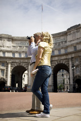A middle-aged couple standing by Admiralty Arch, taking a photograph