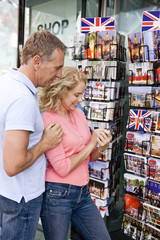 A middle-aged couple looking at postcards outside a souvenir shop