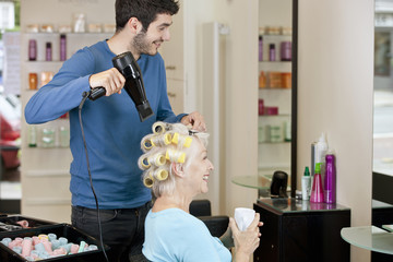 A senior woman drinking a hot beverage whilst having her hair dried by a male hairdresser